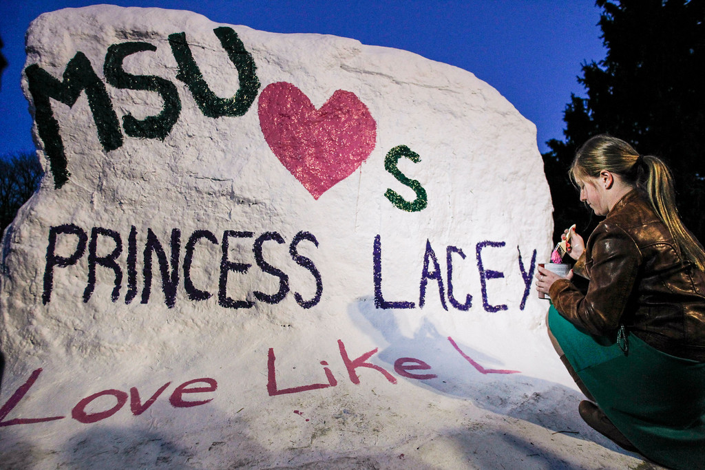 ". MSU kinesiology junior Danielle Bott paints on ""the Rock\"" where  over 100  gathered along the banks of the Red Cedar river on the campus of Michigan State University, Wednesday, April 9, 2014, to honor the legacy of \""Princess Lacey\"" Holsworth, of St. Johns.  The 8-year-old lost her battle with cancer Tuesday evening, April 8, 2014.  Holsworth\'s battle has been nationally publicized due to her close relationship with her \""adopted big brother,\"" MSU senior center Adreian Payne, the MSU men\'s basketball team, and the Spartan community. (AP Photo/Lansing State Journal, Matthew Dae Smith)"