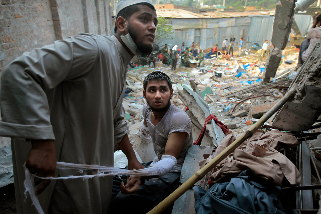 . A Bangladeshi rescuer dresses the wound of another who got injured during a rescue operation at the site of a building that collapsed Wednesday in Savar, near Dhaka, Bangladesh, Thursday, April 25, 2013. (AP Photo/A.M.Ahad)