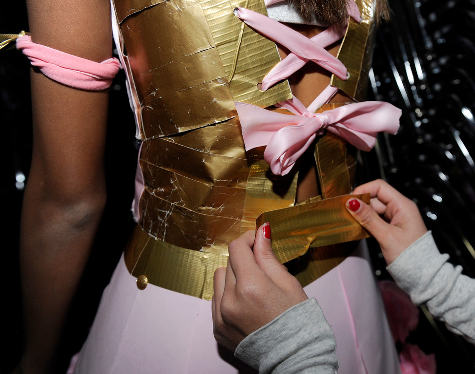 . Jacel Davis one of the designers adds a piece of gold duct tape to finish off and secure the bodice of this dinner party dress modeled by Chelsea Correa at the third annual Paper Skirt Fashion Show held at Liberty High School in Brentwood, Calif.  on Tuesday, Jan. 29, 2013.  (Susan Tripp Pollard/Staff)