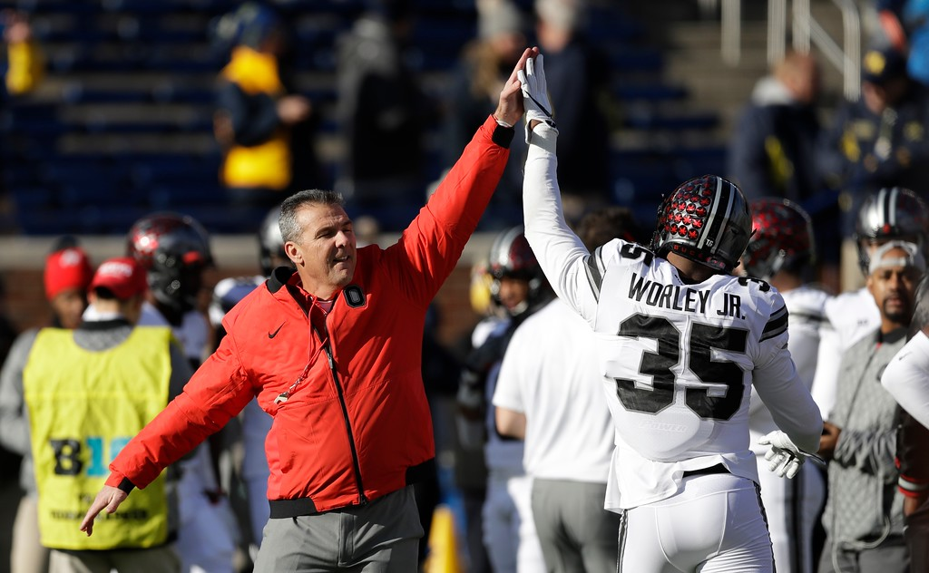 . Ohio State head coach Urban Meyer high fives Ohio State linebacker Chris Worley (35) during warmups an NCAA college football game against Michigan, Saturday, Nov. 25, 2017, in Ann Arbor, Mich. (AP Photo/Carlos Osorio)