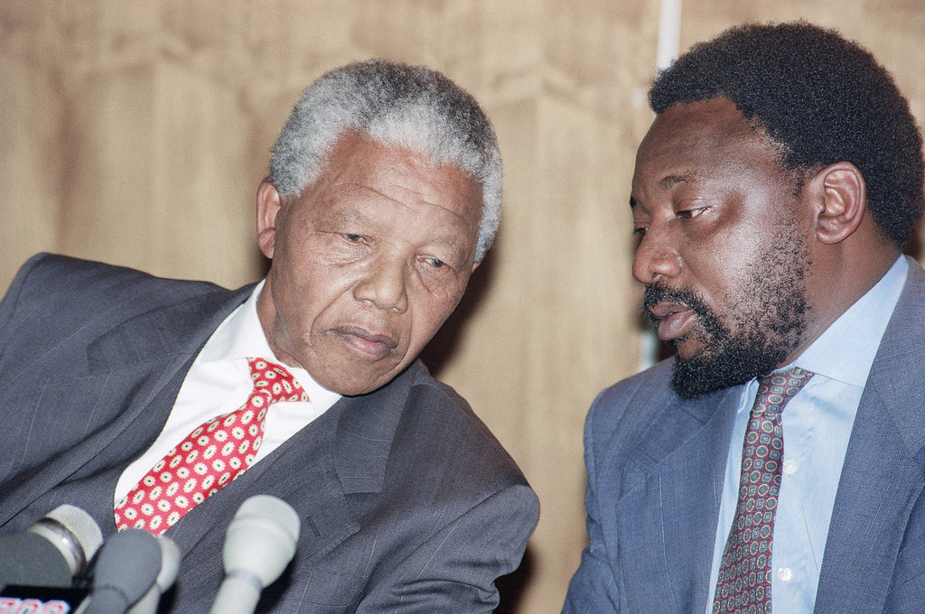 . African National Congress President Nelson Mandela (left) and secretary general Cyril Ramaphose (right) confide in one another at a news conference in Johannesburg on Monday, August 30, 1993, where the ANC apologized for abuses caused to members in prison camps outside South Africa. (AP Photo/Denis Farrell)