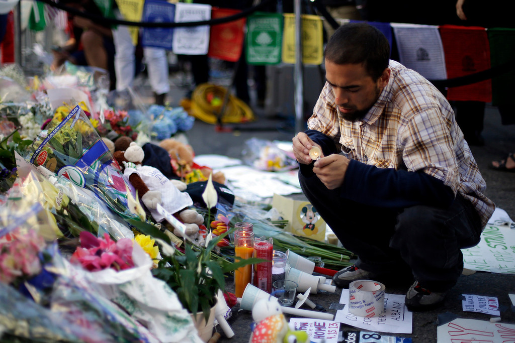 . Richard Maldonado lights a candle at a makeshift memorial on Boylston Street near the finish line of Monday\'s Boston Marathon explosions, which killed at least three and injured more than 140,  Wednesday, April 17, 2013, in Boston. (AP Photo/Matt Rourke)