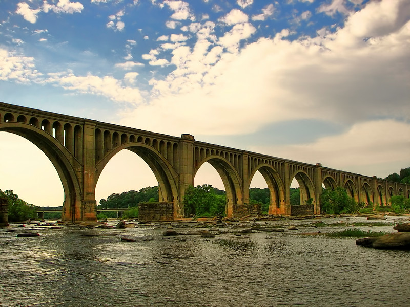 Old arch bridge with beautiful design stretches across a river that is scattered with rocks.