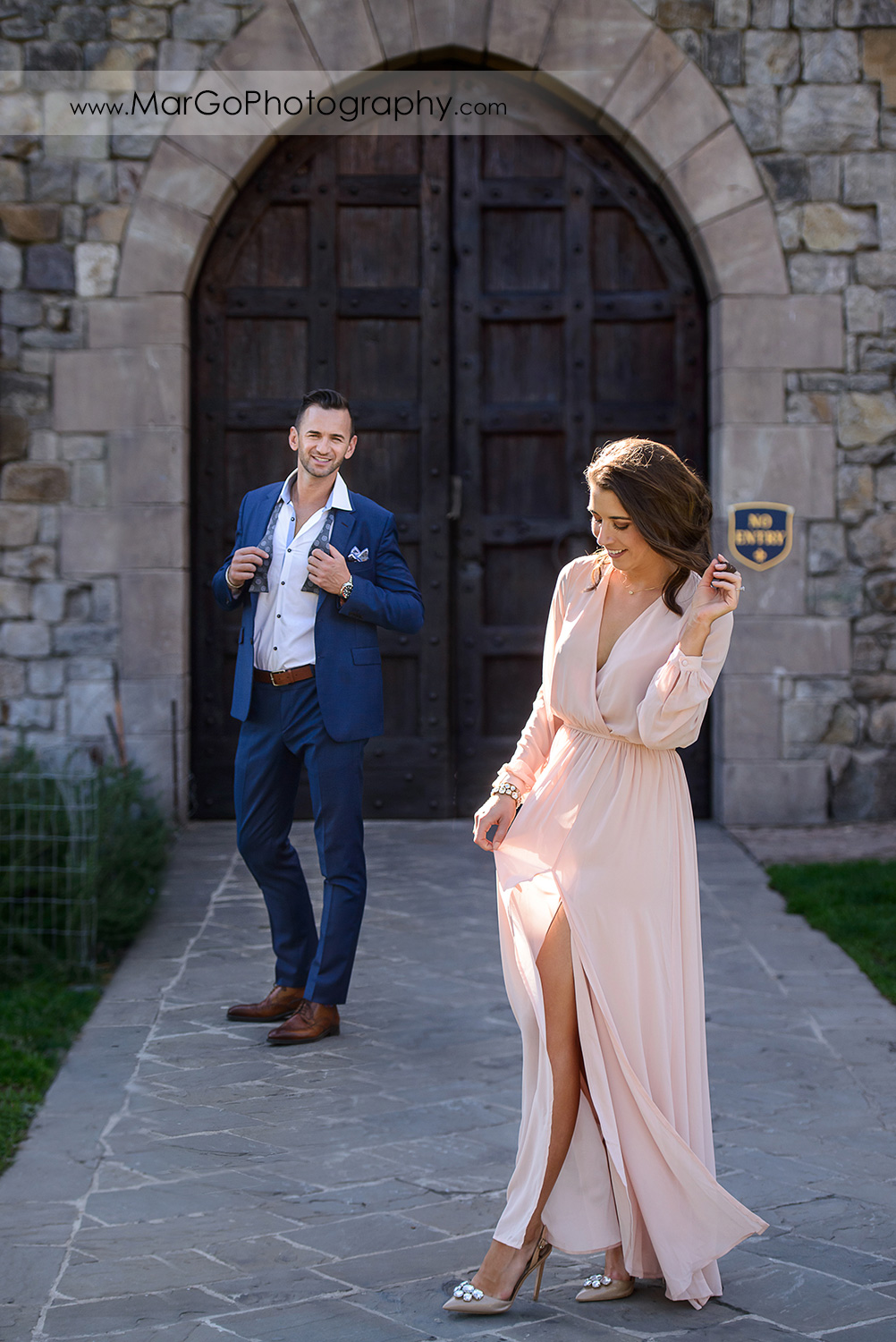 full body portrait of woman in pink dress standing in front of man in blue suit during Napa Valley engagement session at Castello di Amorosa in Calistoga