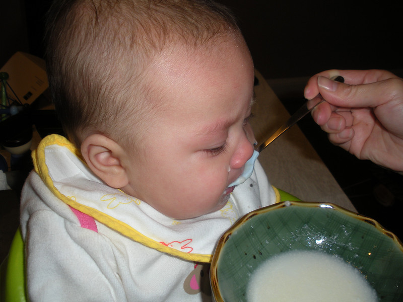 Eating from a spoon for the first time.