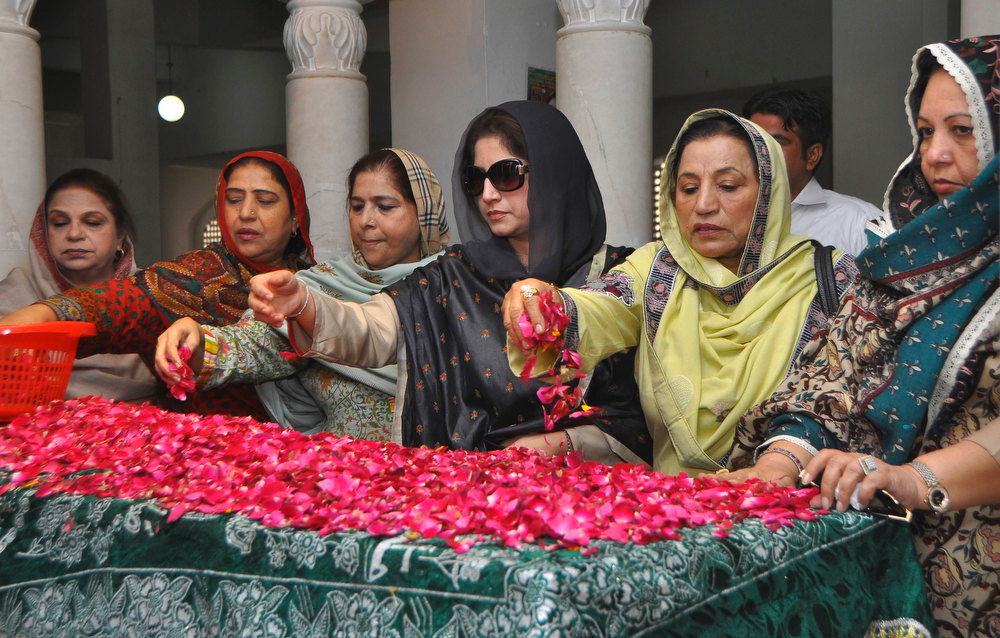 Description of . Pakistan Peoples Party (PPP) supporters scatter rose petals on the grave of Pakistan's former Prime Minister Benazir Bhutto during her death anniversary at the Bhutto family mausoleum in Garhi Khuda Bakhsh, near Larkana December December 27, 2012. Bhutto was killed in a gun and suicide bomb attack after an election rally in the city of Rawalpindi on December 27, 2007, weeks after she returned to Pakistan after years in self-imposed exile. REUTERS/Nadeem Soomro