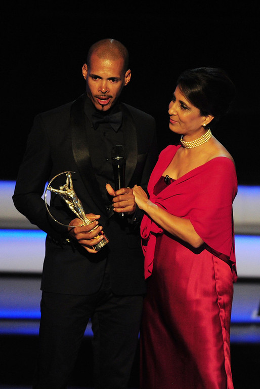 """. Athlete Felix Sanchez accepts his award for \""""Laureus World Comebcak of the Year\""""  from Laureus Academy Member Nawal El Moutawakel during the awards show for the 2013 Laureus World Sports Awards at the Theatro Municipal Do Rio de Janeiro on March 11, 2013 in Rio de Janeiro, Brazil.  (Photo by Jamie McDonald/Getty Images For Laureus)"""