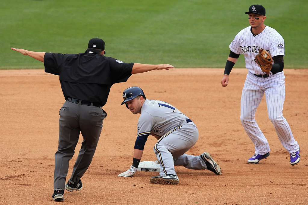 . Caleb Gindl #15 of the Milwaukee Brewers slides safely into second base with a double as shortstop Troy Tulowitzki #2 of the Colorado Rockies watches umpire Doug Eddings make the call in the second inning at Coors Field on July 28, 2013 in Denver, Colorado.  (Photo by Doug Pensinger/Getty Images)