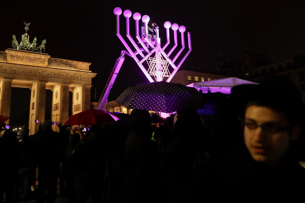 . A giant Hanukkah Menorah set up by the Jewish Chabad Educational Center, is illuminated at the Pariser Platz in front of the Brandenburg Gate in Berlin, Tuesday, Dec. 12, 2017. (AP Photo/Markus Schreiber)