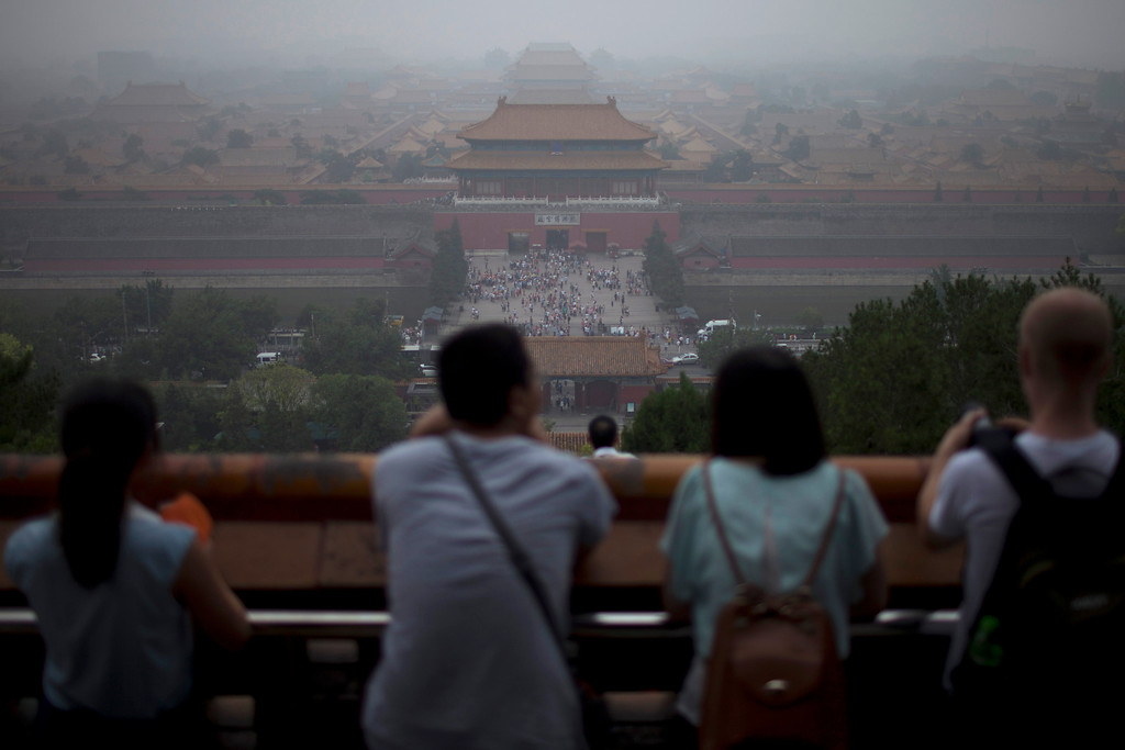 """. In this photo taken on June 29, 2013, tourists look at the Forbidden City from the top of Jinshan hill on a hazy day in Beijing, China. China\'s tourism industry has grown at a fast pace since the country began free market-style economic reforms three decades ago. However, it\'s latest tourism slogan \""""Beautiful China\"""" has been derided as particularly inept at a time when record-busting smog has drawn attention to the environmental and health costs of China\'s unfettered industrialization. Some point to unsophisticated marketing as an explanation.  (AP Photo/Alexander F. Yuan)"""