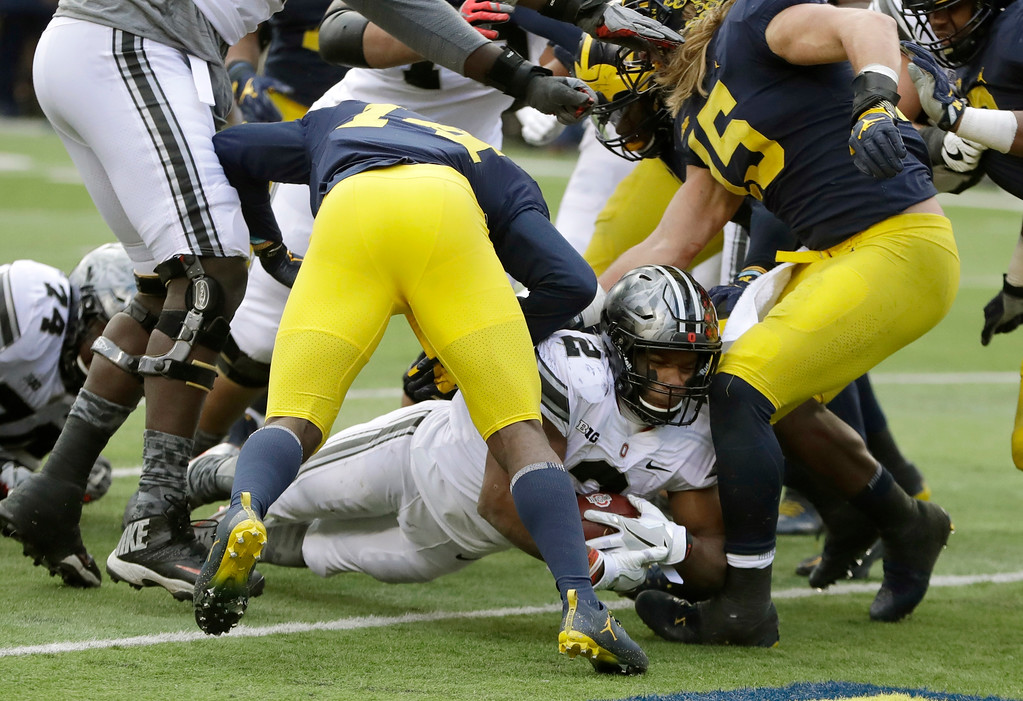 . Ohio State running back J.K. Dobbins breaks through the Michigan defense for a one-yard rush for a touchdown during the second half of an NCAA college football game, Saturday, Nov. 25, 2017, in Ann Arbor, Mich. (AP Photo/Duane Burleson)