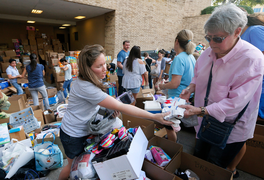 . Christina Landrum, center, of The Woodlands, Texas, accepts a donation of clothing as she helps organize the tons of items donated at a North Dallas collection point, Tuesday, Aug. 29, 2017. Landrum, who lives in the Houston suburb, is an evacuee and said she wanted to help anyway she could. (AP Photo/Tony Gutierrez)