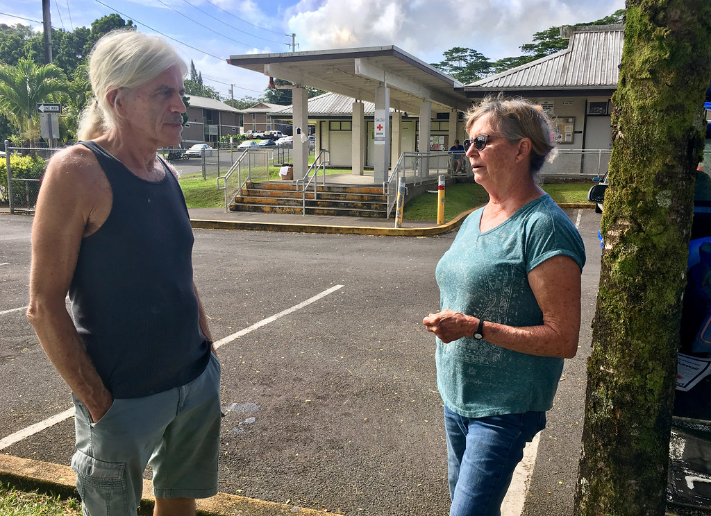 . Michael McGuire, who lives in the Leilani Estates subdivision where the first lava erupted right behind his home, talks to Cherie McArthur at a shelter in Pahoa, Hawaii on Sunday, May 6, 2018. Officials on Hawaii\'s Big Island say what started out as a small spattering of lava from the ground Saturday night only took minutes to become cascading fountains. U.S. Geological Survey volcanologist Wendy Stovall says lava fountains spewed as high as 230 feet (70 meters) into the air only 15 minutes after the initial eruption from a the latest of several new fissures in the area. (AP Photo/Haven Daley)