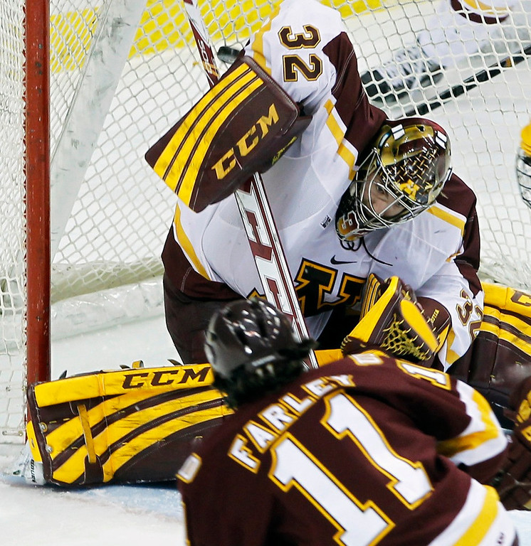 . Bulldogs left wing Austin Farley, bottom, scores on Gophers goalie Adam Wilcox during the first period. (AP Photo/Ann Heisenfelt