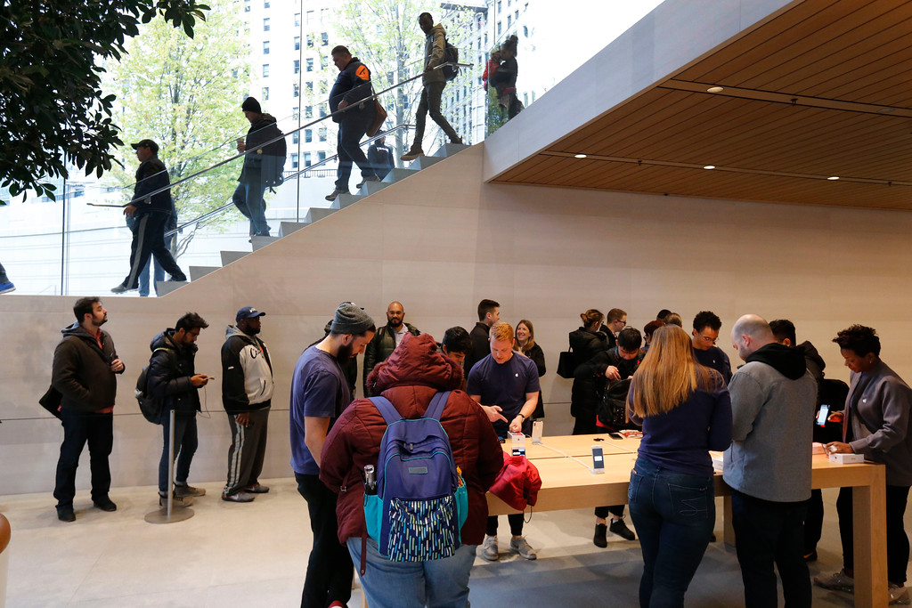 . Consumers descend into the new Apple Michigan Avenue store along the Chicago River as others try out the Apple iPhone X Friday, Nov. 3, 2017, in Chicago. (AP Photo/Charles Rex Arbogast)