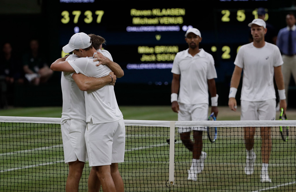 . Mike Bryan and Jack Sock of the United States hug after winning their men\'s doubles final match against South Africa\'s Raven Klaasen and New Zealand\'s Michael Venus at the Wimbledon Tennis Championships, in London, Saturday July 14, 2018.(AP Photo/Ben Curtis)