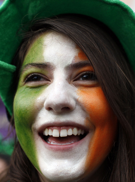 . A spectator with the flag of Ireland painted on her face watches the parade during St Patrick\'s Day festivities in Dublin on March 17, 2014. More than 100 parades are being held across Ireland to mark St Patrick\'s Day, the feast day of the patron saint of Ireland, with up to 650,000 spectators expected to attend the parade in Dublin. AFP PHOTO/ PETER MUHLY/AFP/Getty Images