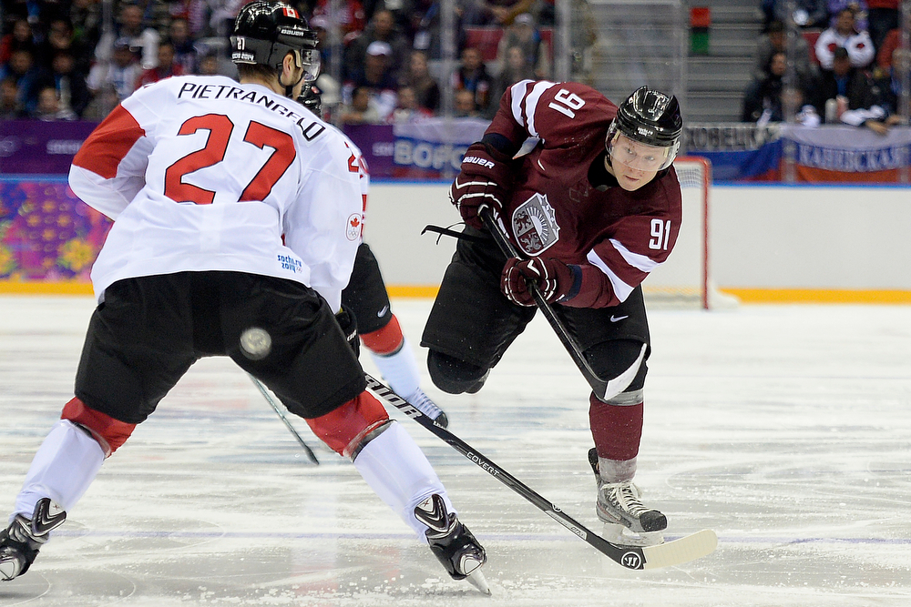 . Ronalds Kenins (91) of the Latvia takes a shot as Alex Pietrangelo (27) of the Canada defends during the second period of men\'s hockey action. Sochi 2014 Winter Olympics on Wednesday, February 19, 2014 at Bolshoy Ice Arena. (Photo by AAron Ontiveroz/ The Denver Post)