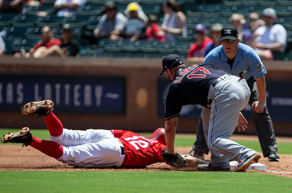 . Texas Rangers\' Rougned Odor (12) dives back to first base under the tag of Cleveland Indians first baseman Yonder Alonso (17) during the first inning of a baseball game Sunday, July 22, 2018, in Arlington, Texas. (AP Photo/Sam Hodde)