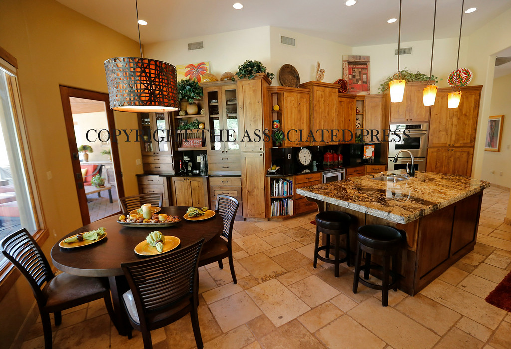 . This is an interior view of a luxury home with a listing price of $1 million on Wednesday, July 30, 2014 in Mesa, Ariz. The more than 4,000-square-foot home has a resort style back yard, pool and hot tub, four bedrooms, three full and one partial bathrooms, a gourmet kitchen and travertine tile throughout the home. (AP Photo/Matt York)