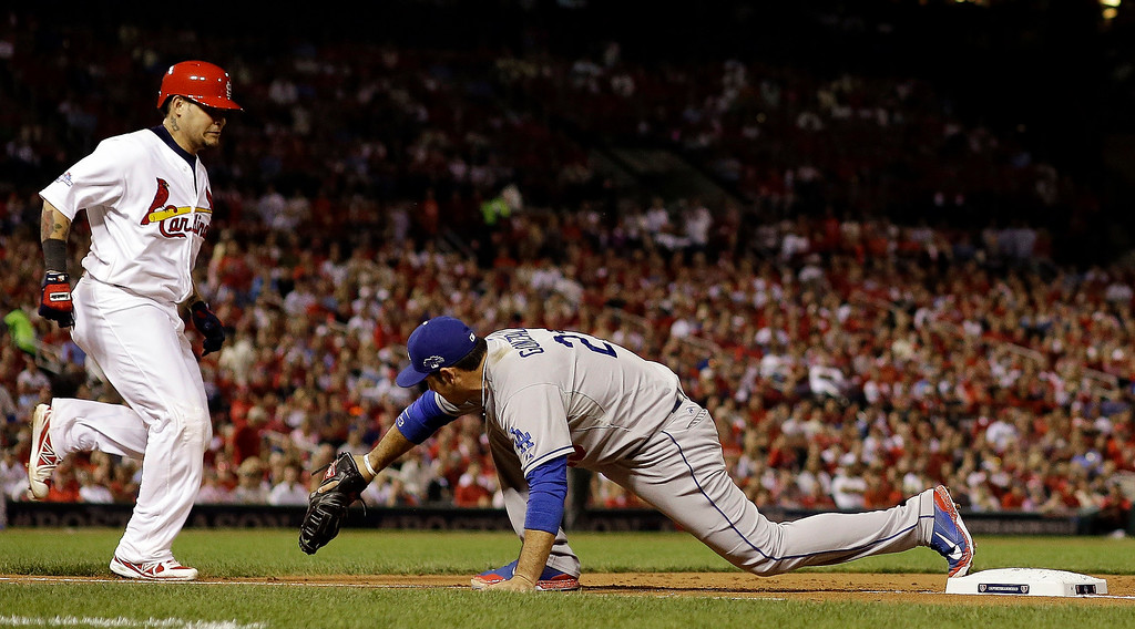 . Los Angeles Dodgers first baseman Adrian Gonzalez stretches to get St. Louis Cardinals\' Yadier Molina out at first during the second inning of Game 1 of the National League baseball championship series Friday, Oct. 11, 2013, in St. Louis. (AP Photo/Jeff Roberson)