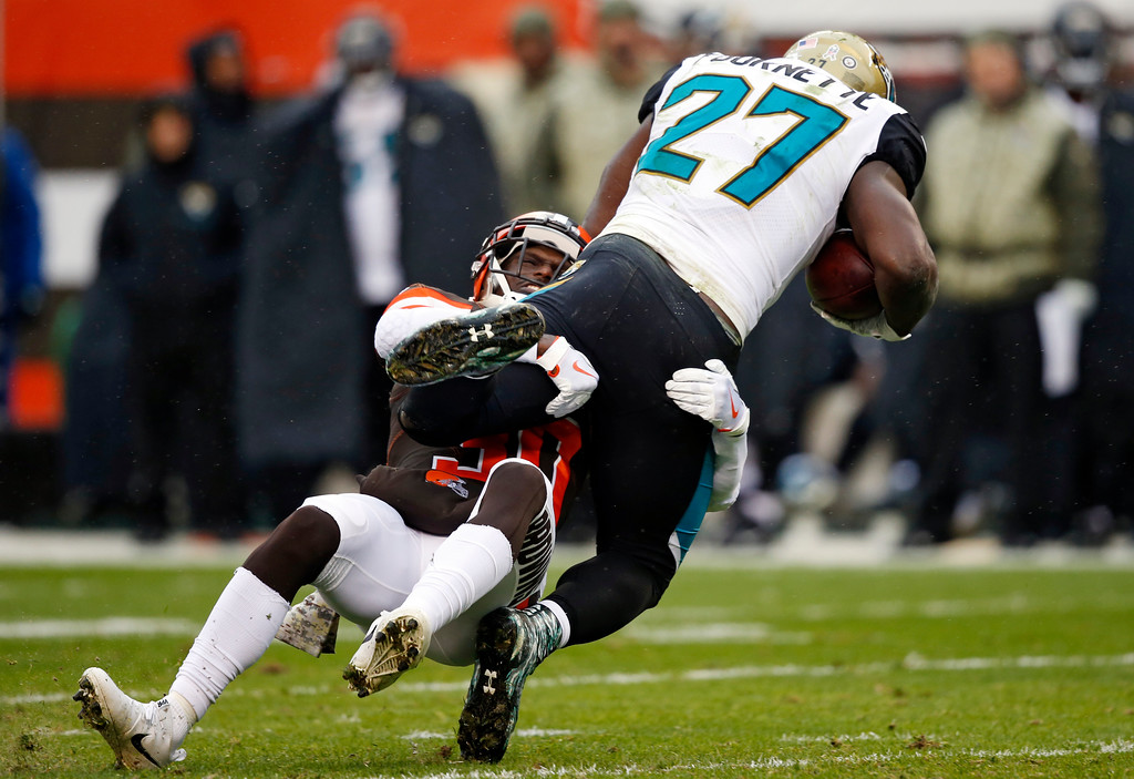 . Cleveland Browns defensive back Jason McCourty (30) tackles Jacksonville Jaguars running back Leonard Fournette (27) in the first half of an NFL football game, Sunday, Nov. 19, 2017, in Cleveland. (AP Photo/Ron Schwane)
