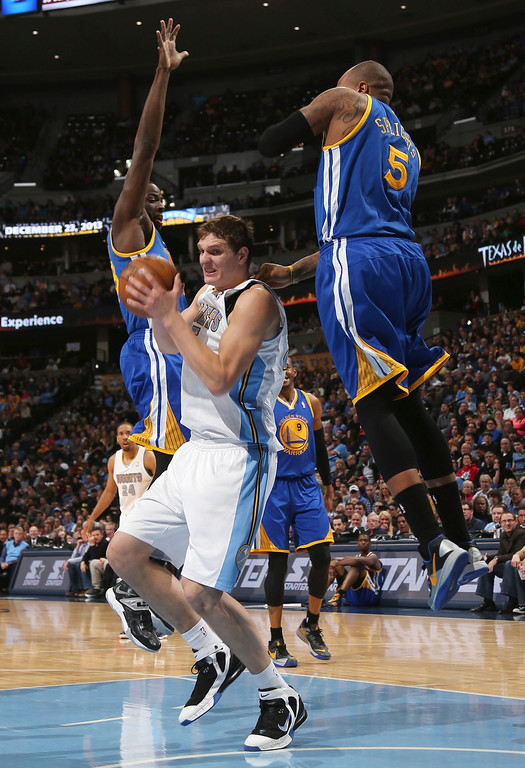 . Denver Nuggets center Timofey Mozgov, center, of Russia, tries to drive the lane for a shot as Golden State Warriors forwards Draymond Green left, and Marreese Speights defend during the third quarter of the Warriors\' 89-81 victory in an NBA basketball game in Denver on Monday, Dec. 23, 2013. (AP Photo/David Zalubowski)