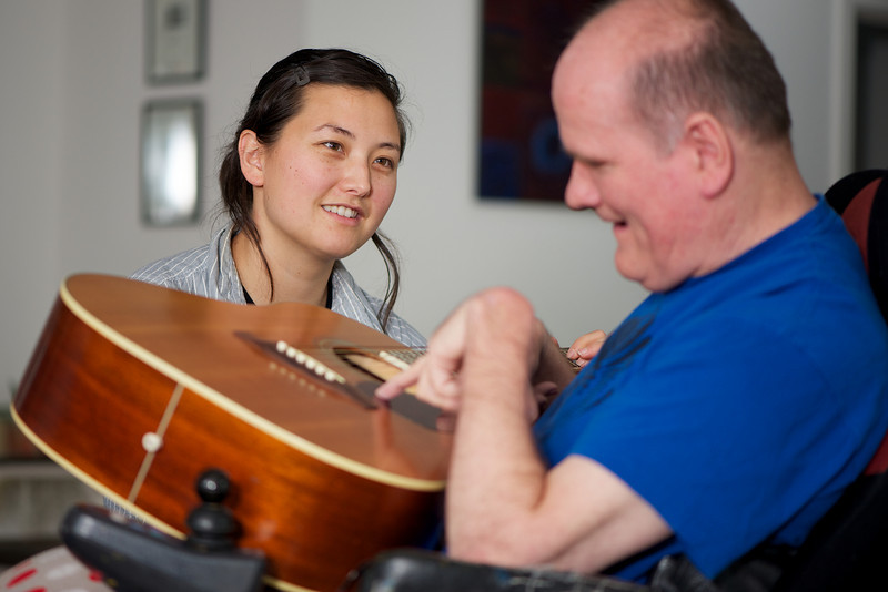 """This photo was made at the man's home, where he was participating in a music session with a staff member.    This photo can be used to illustrate the importance of promoting engagement in meaningful activity.  This whole concept and practice has been referred to as Person-Centred Active Support and has extensive empirical evidence to support its importance in promoting a great quality of life for all people with a disability, """"irrespective of degree of disability or the presence of extra problems*  * Mansell, J., Beadle-Brown, J., Ashman, B., & Ockenden, J. (2004). Person-Centred Active Support. Pavilion Publishing (Brighton) Ltd.."""