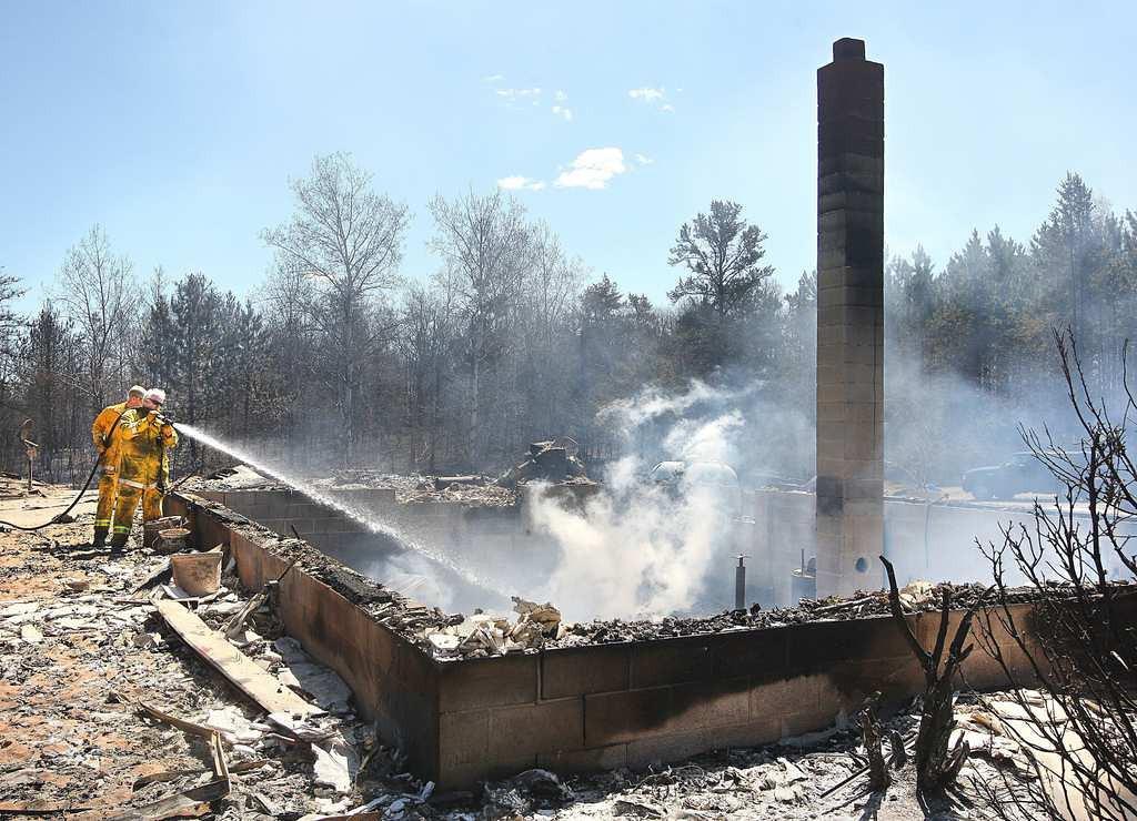 . Spooner volunteer firefighters spray down a hot spot inside a foundation on Murray Lake Road near Barnes, Wis. (Associated Press/Duluth News-Tribune: Bob King)
