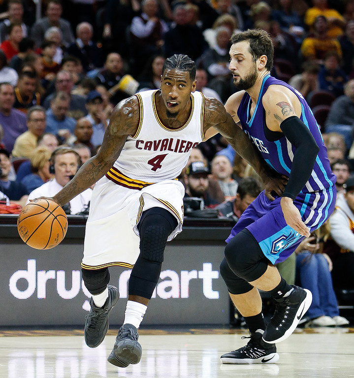 . Cleveland Cavaliers\' Iman Shumpert (4) drives around Charlotte Hornets\' Marco Belinelli during the first half of an NBA basketball game Sunday, Nov. 13, 2016, in Cleveland. (AP Photo/Ron Schwane)