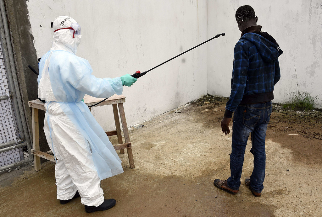 . A visitor is decontaminated by a health worker at Island Hospital as he arrives to deliver food to relatives suffering from the Ebola virus in Monrovia on September 26, 2014. PASCAL GUYOT/AFP/Getty Images