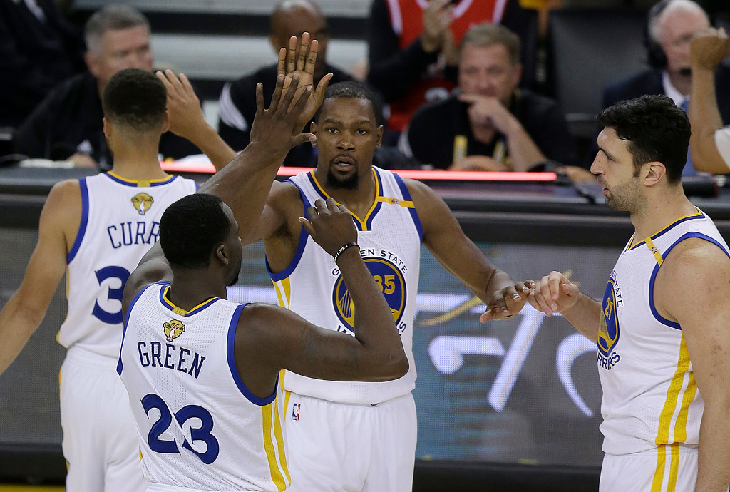 . Golden State Warriors forward Kevin Durant, center, celebrates with guard Stephen Curry, top left, forward Draymond Green (23) and center Zaza Pachulia during the second half of Game 2 of basketball\'s NBA Finals against the Cleveland Cavaliers in Oakland, Calif., Sunday, June 4, 2017. (AP Photo/Ben Margot)