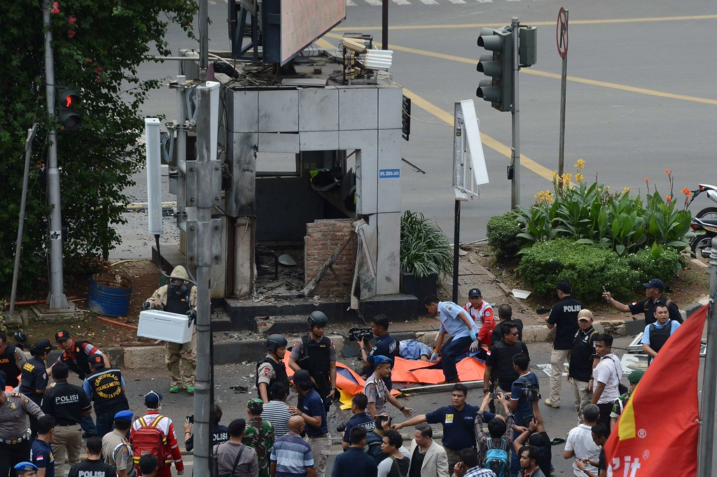""". Indonesian police secure the scene next to victims (C-in orange body bags) outside a traffic police outpost after a series of explosions hit central Jakarta on January 14, 2016.  Gunfire and explosions in the Indonesian capital Jakarta killed at least four people on January 14 in what the country\'s president dubbed \""""acts of terror\"""", with fears that militants were still on the run.     AFP PHOTO / ROMEO GACAD/AFP/Getty Images"""