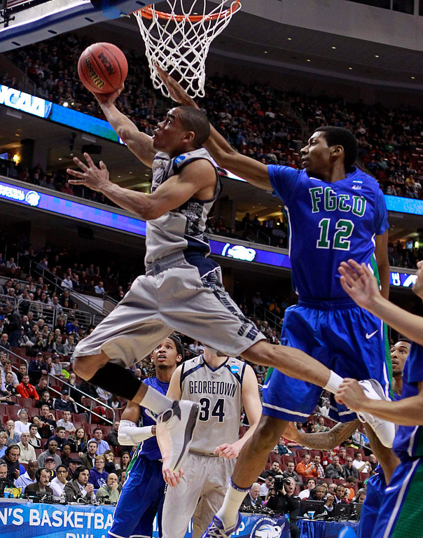 . Georgetown Hoyas\' Markel Starks (front L) shoots under pressure from Florida Gulf Coast Eagles\' Eric McKnight during the first half of their second round NCAA tournament game in Philadelphia, Pennsylvania March 22, 2013. REUTERS/Tim Shaffer