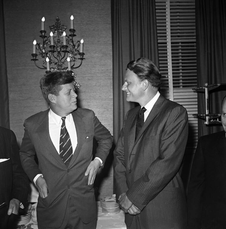 ". President John F. Kennedy talks with evangelist Billy Graham at the annual ""Presidential Prayer Breakfast\"" in a Washington hotel, Feb. 9, 1961.  (AP Photo)"