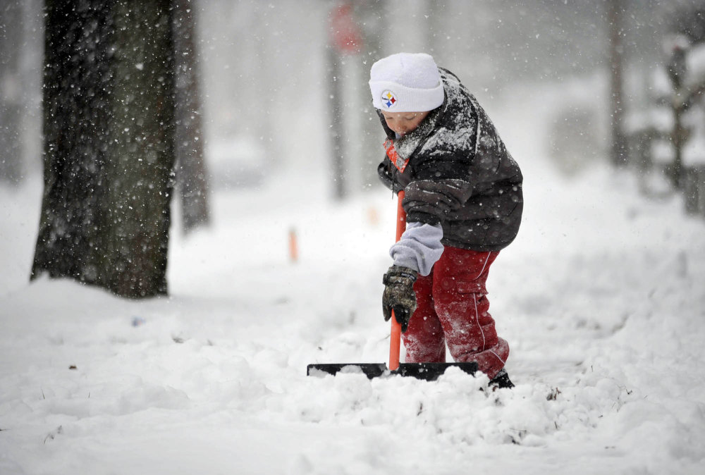 Description of . Aaden Cummings,8, shovels the sidewalk in front of his house in the Johnstown, Pa., suburb of Ferndale, during a winter storm on Wednesday, Dec. 26, 2012. (AP Photo/The Tribune-Democrat, John Rucosky)