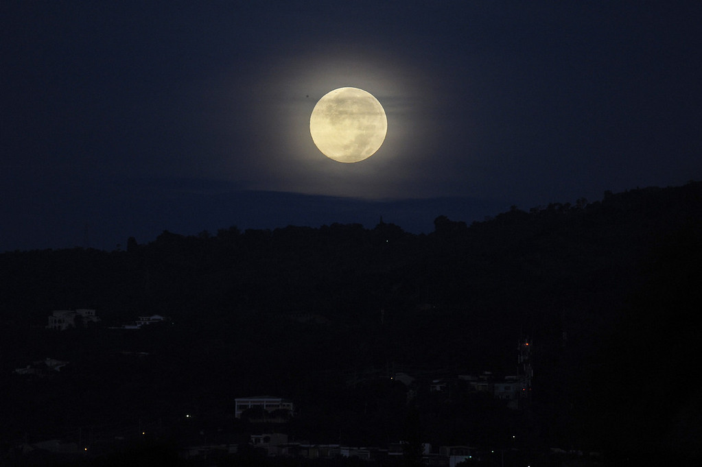 ". A full moon rises over San Salvador, El Salvador on June 23, 2013. This ""super moon\"" also known as a \""perigee\"" full moon appears about 14 percent larger and 30 percent brighter than a regular full moon, according to NASA scientists.  Jose CABEZAS/AFP/Getty Images"