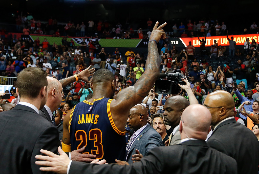. Cleveland Cavaliers forward LeBron James (23) waves to the crowd as he is escorted off the court by security officials after defeating Atlanta Hawks in Game 4 of the second-round NBA basketball playoff series, Sunday, May 8, 2016, in Atlanta. Cleveland won 100-99 and won the best-of-seven series 4-0. (AP Photo/John Bazemore)