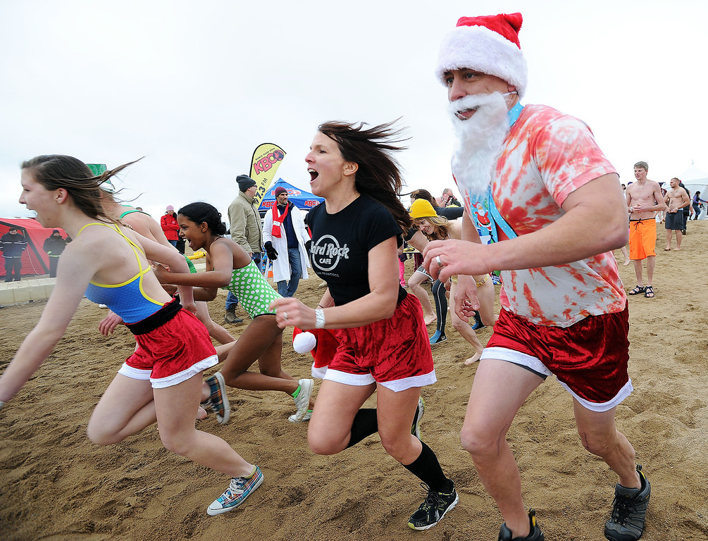 . Bailey Mooney, left, Mekdes Disho, Michaela Mooney and Kevin Mooney, enter the icy water on Wednesday. The 31st annual Boulder Polar Plunge, at the Boulder Reservoir on New Year�s Day, to help the Boulder County AIDS Project and connectBCAP.  Cliff Grassmick/Daily Camera