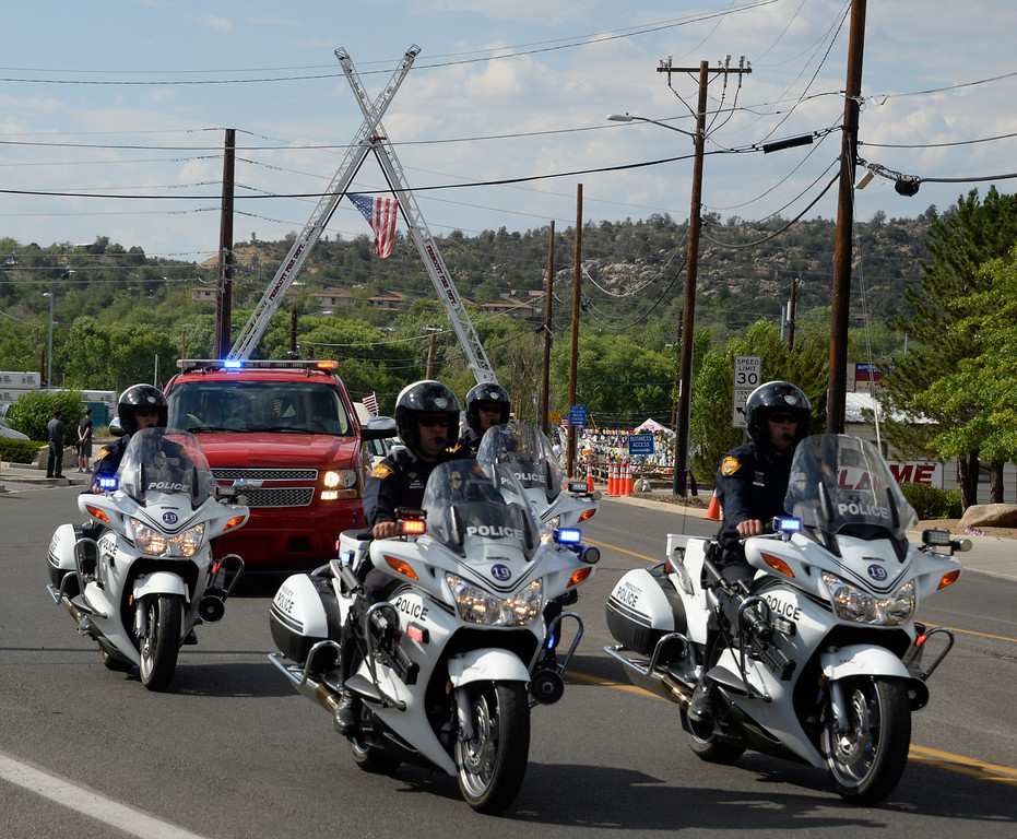 . July 7,2013. Prescott AZ-USA.  A procession of hearses carrying the remains of 19 members of the Granite Mountain Hotshot firefighting team who were killed fighting the Yarnell Fire a week ago move through Prescott July 7, 2013. The convoy to pass beneath crossed fire ladders on a street flanked with fire trucks  about 100 miles north of Phoenix. The final services for the firefighter will be on Tuesday in Prescott AZ as people still visit the memorial wall at the fire station.  Photo  by Gene Blevins/LA Daily News