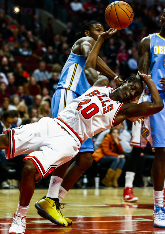 . Chicago Bulls forward Tony Snell (R) is shoved to the floor by Denver Nuggets forward Kenneth Faried who was called for a flagrant foul in the second half of their NBA game at the United Center in Chicago, Illinois, USA, 21 February 2014. The Bulls defeated the Nuggets.  EPA/TANNEN MAURY