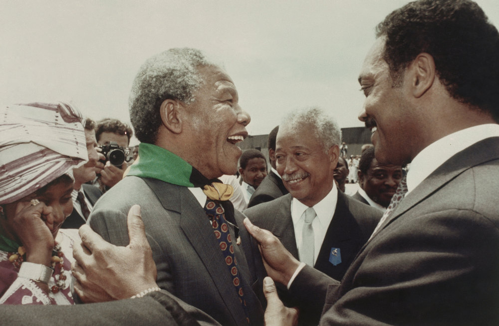 Description of . Nelson Mandela, accompanied by his wife, Winnie, far left, is greeted by Rev. Jesse Jackson, right, at Kennedy Airport, in New York on June 20, 1990. At center is New York City Mayor David N. Dinkins, who also welcomes Mandela at the outset of a three-day visit to the city. (AP Photo/Chester Higgins Jr.)