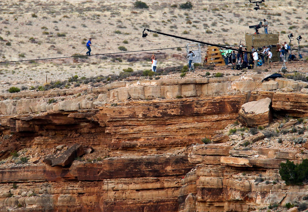 . Daredevil Nik Wallenda walks on a two-inch (5-cm) diameter steel cable rigged 1,400 feet  (426.7 metres) across more than a quarter-mile deep remote section of the Grand Canyon near Little Colorado River, Arizona June 23, 2013.  REUTERS/Mike Blake