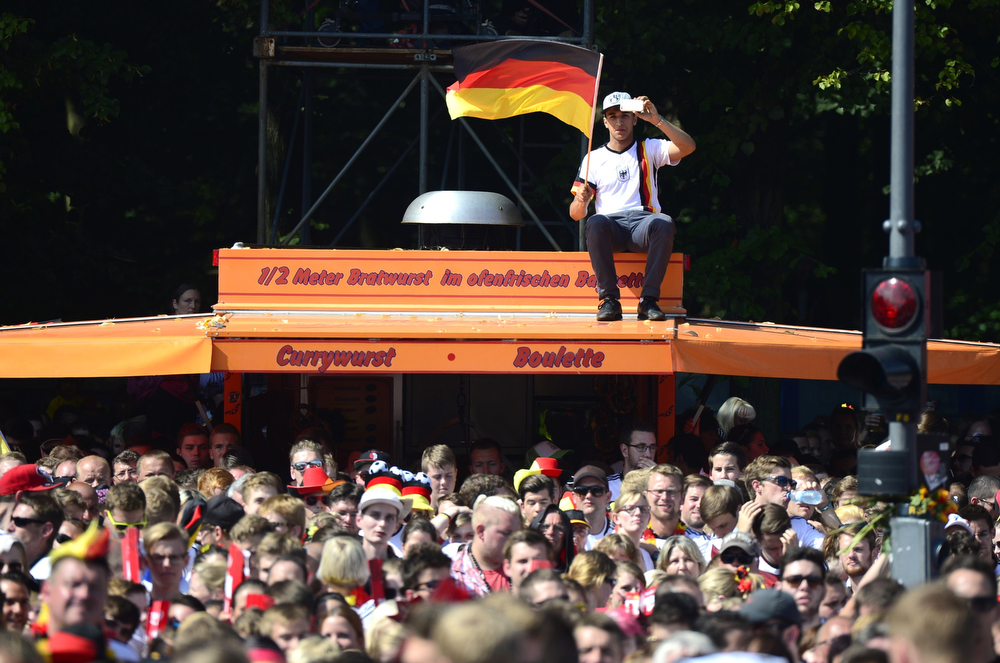 . German fans await the arrival of the German national team at Berlin\'s landmark Brandenburg Gate to celebrate their FIFA World Cup title. Germany won their fourth World Cup title, after 1-0 win over Argentina on July 13, 2014 in Rio de Janeiro in the FIFA World Cup Brazil final game. (CLEMENS BILAN/AFP/Getty Images)