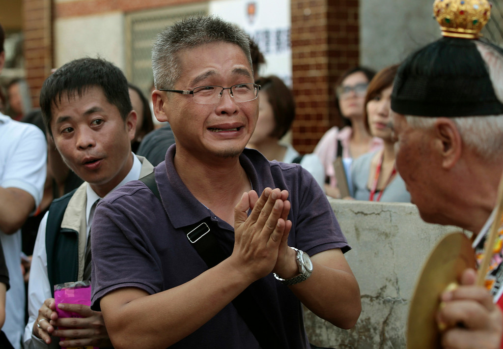 . A relative of a victim killed in the TransAsia Airways Flight GE222 crash prays at a makeshift altar at the crash site on the outlying island of Penghu, Taiwan, Thursday, July 24, 2014.  (AP Photo/Wally Santana)