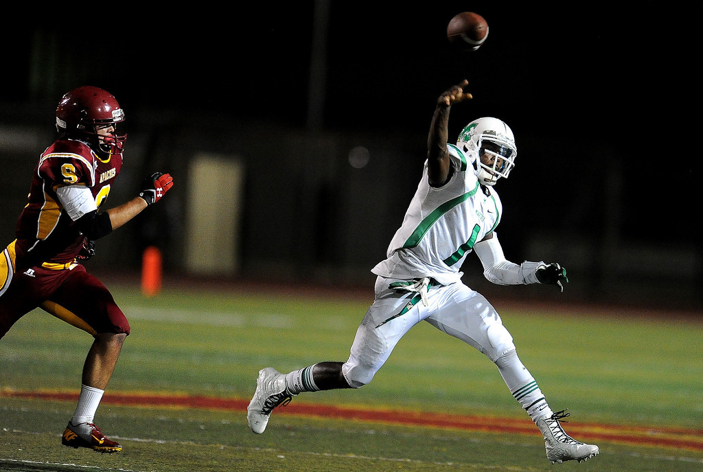 . Monrovia quarterback Deshawn Potts (1) passes ahead of Arcadia\'s Joe Haines (9) in the first half of a prep football game at Arcadia High School in Arcadia, Calif. on Friday, Sept. 13, 2013.   (Photo by Keith Birmingham/Pasadena Star-News)