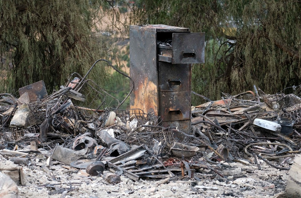. The charred remains of a burned out home are seen Monday, Sept. 4, 2017, in the Sunland-Tujunga section of Los Angeles. Wildfires forced thousands to flee their homes across the U.S. West during a sweltering, smoke-shrouded holiday weekend of record heat. (AP Photo/Ringo H.W. Chiu)