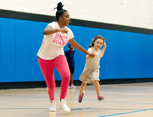 09/06/18 Wesley Bunnell | Staff Nikira Hooks, L, helps Neljia Djakun run home during a game of kickball at the Boys & Girls Club of New Britain on Thursday afternoon. The club's after school programs have opened earlier than normal to accommodate school children during the CSDNB's decision to start the school year off on half days due to excessive heat.
