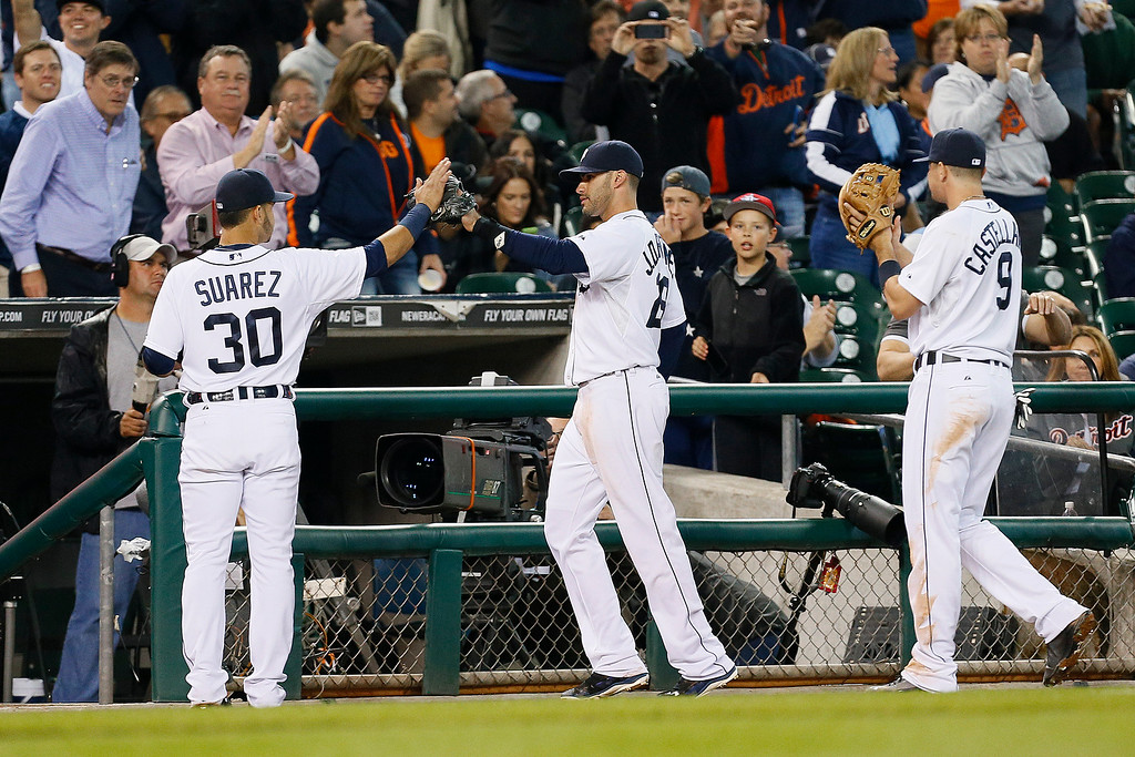 . Detroit Tigers left fielder J.D. Martinez, center, is congratulated by Eugenio Suarez (30) and Nick Castellanos (9) after catching a Chicago White Sox catcher Josh Phegley fly ball at the outfield wall in the fifth inning of a baseball game in Detroit Tuesday, Sept. 23, 2014. (AP Photo/Paul Sancya)