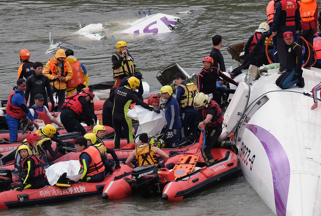 . Rescue personnel in a rubber dinghy lift two bodies from the wreckage of a TransAsia ATR 72-600 turboprop plane that crash-landed into the Keelung river outside Taiwan\'s capital Taipei in New Taipei City on February 4, 2015. At least 16 people were killed when TransAsia Airways Flight GE235 with 58 people on board clipped a road bridge and plunged into the river in Taiwan, in the airline\'s second crash in just seven months.    AFP PHOTO / SAM YEHSAM YEH/AFP/Getty Images